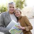 Senior couple in town looking at map and tablet — Stock Photo #26964915
