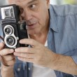 Senior photographer holding vintage camera — Stock Photo