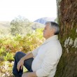 Senior man relaxing in nature, leant againt tree — Foto Stock
