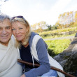 Closeup of happy senior couple sitting by river — Stock Photo #26965019