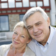 Smiling senior couple standing in home garden — Stock Photo