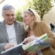 Senior couple in town looking at map and tablet — Stock Photo #26965059