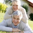 Smiling senior couple laying down the grass — Foto Stock