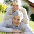 Smiling senior couple laying down the grass — Stockfoto