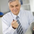 Portrait of senior businessman in office using tablet — Stock Photo #26965117