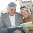 Senior couple in town looking at map and tablet — Stock Photo #26965169