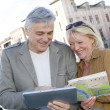 Stock Photo: Senior couple in town looking at map and tablet