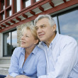 Senior couple sitting in front of house and looking away — Stock Photo