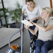 Young woman helping disabled lady at home — Stock Photo