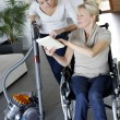 Young woman helping disabled lady at home — Stock Photo #26965219