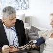 Doctor taking blood pressure to patient at home — Stock Photo
