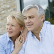 Senior couple sitting in front of house and looking away — Stock Photo #26965323