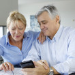 Senior couple calculting bills amount using smartphone — Stock Photo