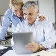 Senior couple looking at bank account on digital tablet — Stock Photo