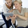 Girl showing tablet to elderly woman in wheelchair — Stock fotografie