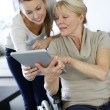 Girl showing tablet to elderly woman in wheelchair — Stockfoto