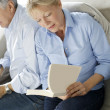 Senior woman reading book, husband sitting beside her — Stock Photo