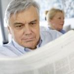 Senior man at home reading newspaper — Stock Photo