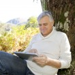 Senior man leant againt tree websurfing on internet with tablet — Stock Photo