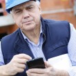 Entrepreneur on construction site using smartphone — Stock Photo