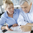 Stockfoto: Senior couple inquiring bank website for help