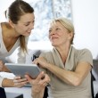 Girl showing tablet to elderly woman in wheelchair — Stock Photo