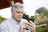 Senior hombre usando smartphone en jardín — Foto de Stock