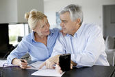 Senior couple calculting bills amount using smartphone — Stockfoto