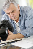 Photographer in office looking at camera screen — Stock Photo