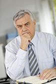 Senior businessman being serious in front of client — Stock Photo