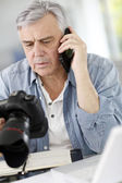 Photographer in office talking on the phone with client — Stock Photo