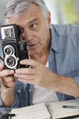 Senior photographer holding vintage camera — Stock Photo