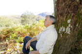 Senior man relaxing in nature, leant againt tree — Stock Photo