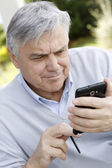 Senior man using smartphone in garden — Stock Photo