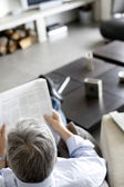 Back view of man reading newspaper at home — Stock Photo