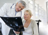 Surgeon showing X-ray result to woman in wheelchair — Stock Photo