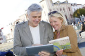Senior couple in town looking at map and tablet — Stock Photo