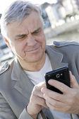 Portrait of senior man using smartphone in town — Stock Photo