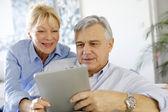 Modern senior couple websurfing on tablet — Stock Photo