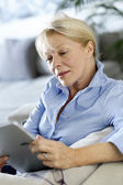 Senior woman using electronic tablet in sofa — Stock Photo