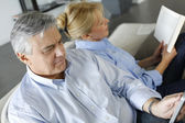Senior couple relaxing at home in sofa — Stock Photo