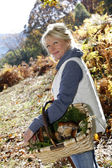 Senior woman in forest holding basket of mushrooms — Stock Photo