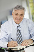 Portrait of senior businessman writing on agenda — Stock Photo