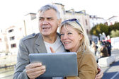Senior couple using digital tablet in touristic area — Stock Photo