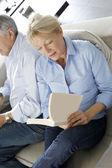 Senior woman reading book, husband sitting beside her — Stock Photo