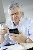Portrait of senior businessman using smartphone — Stock Photo
