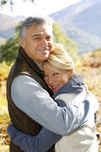 Portrait of smiling senior couple in countryside — Stock Photo