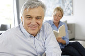Smiling senior man sitting in couch, wife in background — Stock Photo