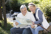 Senior couple sitting by river and looking at map — Stock Photo