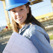 Woman engineer standing on construction site with plan — Stock Photo #26971571